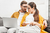 couple with coffee and laptop cuddling on couch at home