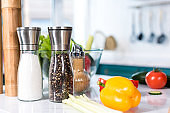 close-up view of fresh vegetables and spices in containers on kitchen table