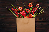 top view of different red vegetables in shopping bag, grocery concept