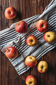 flat lay with arranged ripe apples on linen on wooden surface