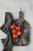 top view of kitchen towel, cutting board and cherry tomatoes on marble table