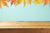 Empty wooden table over autumn leaves blurred background