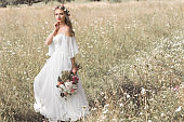 beautiful pensive young bride in wedding dress and floral wreath holding bouquet of flowers while standing outdoors