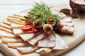 close up of delicious traditional sliced smoked lard with dill and chilli pepper on cutting board