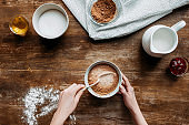 cropped shot of woman preparing liquid for baking pancakes on wooden table