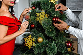 cropped image of couple decorating christmas tree by baubles at home