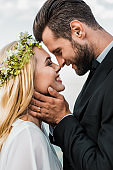 portrait of happy wedding couple in suit and white dress touching with noses on beach