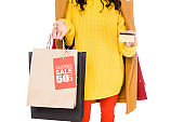 cropped view of stylish shopaholic holding credit card and shopping bags with sale tagisolated on white