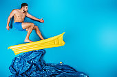 handsome young man in shorts surfing on inflatable mattress on imagine sea on blue