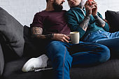 cropped image of tattooed couple drinking coffee at home