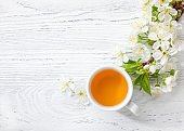 Cup of green tea and  branch of blossom  cherry  on   white  wooden table.