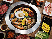 Grilling raw seafood such as mussel, scallop, crab and shrimp on metal grill pan over hot charcoal stove, Japanese barbecue style also know as Yakiniku.