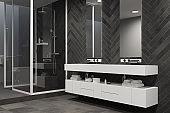 White sink vanity unit in a black bathroom, shower