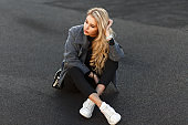 Beautiful fashionable young model woman in a stylish gray coat, black pants and white shoes sits on the asphalt