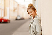 Funny fashionable woman with a smile in a stylish jacket stands near the wall in the city
