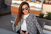 Pretty young stylish woman model in a fashionable jacket with sunglasses sits in a restaurant on the street