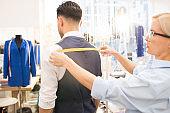 Tailor Measuring Client in Atelier