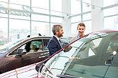 Young Man Choosing New Car in Showroom