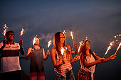 Cheerful friends with sparklers on summer beach