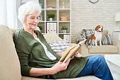 Smiling senior woman reading book at home