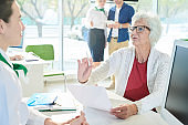 Displeased senior client reading contract in bank office