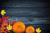 Celebration still life with pumpkins and autumn leaves on wooden background for Thanksgiving