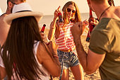 Ecstatic youth drinking alcohol and dancing on beach