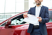 Car Salesman Giving Contract to Client