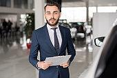 Successful Car Salesman in Showroom