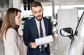 Handsome Car Salesman Talking to Client