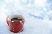 Cup of coffee in snow while snowing