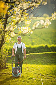 Portrait of senior man gardening, taking care of his lovely orchard,