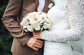 The bride's hand lies on the bridegroom's hand with a wedding bouquet of bride's ring. hands newlyweds