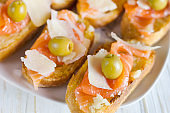 A fresh salmon sandwich with cheese on white plate.