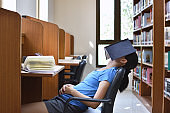 Student sleeping with book in the library