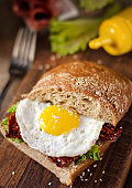 Sandwich with dark bread, dried tomatoes and egg.