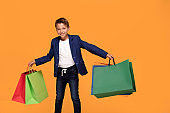 Little boy with colorful shopping bags smiling.
