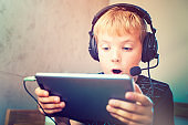Boy with headphones is watching a movie on the tablet.
