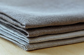 Manufactures industrial textile - grey towels pile isolated on wooden background.