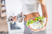 The sport figure of a attractive woman holding bowl from fresh vegetable salad and dumbbell.