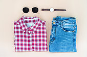 flat lay of woman clothes and accessories set with glasses, watch. Trendy fashion female background.