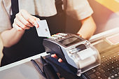 Concept of technology in buying without using cash. Close up of hand use credit card swiping machine to pay.