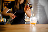 barista prepares a cocktail and pours orange juice into glass