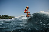 High blue wave on a foreground and young blonde woman wakesurfing on board