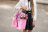 Little school girl dressed in school uniform holding a bright pink festive bouquet