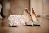 shoes of the bride with shiny pebbles stand next to a white clutch
