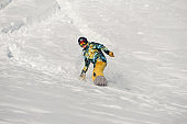 Young snowboarder in bright sportswear riding down a snow hill on bright winter day