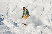 Young snowboarder in bright sportswear riding down a powder mountain slope