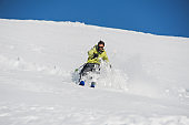 Young active skier in bright yellow sportswear riding down the mountains