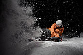 Snowboarder in orange jacket riding on a snowy hill at night